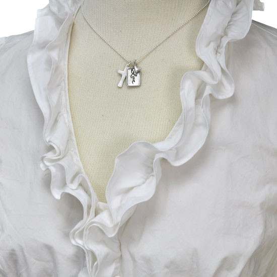 Silver charm with raised edge & the handwritten word Love, with a fine silver cross and fine silver heart, shown on a neckform