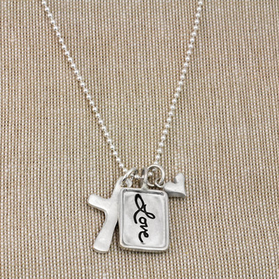Silver charm with raised edge & the handwritten word Love, with a fine silver cross and fine silver heart, shown from the top