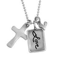 Silver charm with raised edge & the handwritten word Love, with a fine silver cross and fine silver heart, shown close up on white