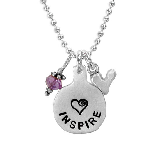Silver necklace hand stamped with the word Inspire and a heart, with a birthstone and a silver heart charm hung on a silver chain, shown close up
