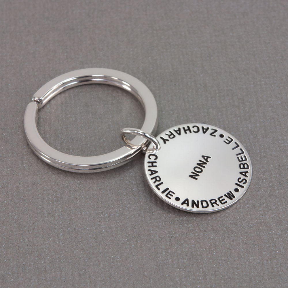Silver custom hand stamped key ring for Nona with grandkids' names, shown from the side