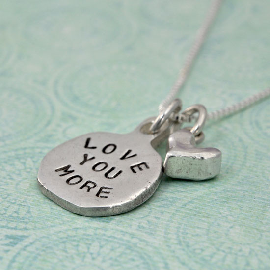 Silver necklace Hand Stamped with the words Love You More , and a silver heart charm, shown on green from the side