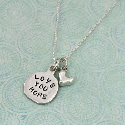 Silver necklace Hand Stamped with the words Love You More , and a silver heart charm, shown on green