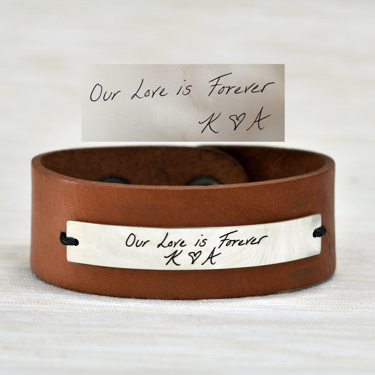 Light brown leather handwriting cuff, shown with handwritten message engraved on silver plate