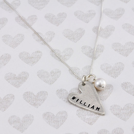 handmade long silver heart charm, hand stamped with a name, hung with a pearl , on a silver chain, shown from above