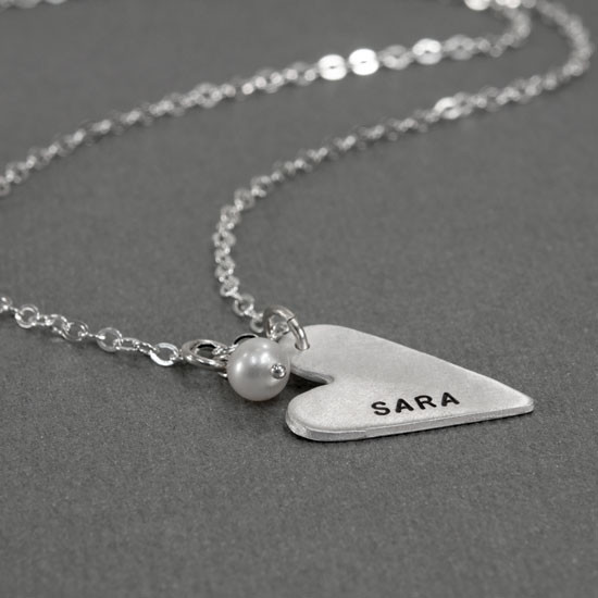 handmade long silver heart charm, hand stamped with a name, hung with a pearl , on a silver chain, shown from the side