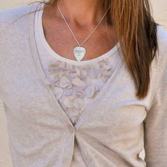 Personalized guitar pick as a necklace, shown on a female model