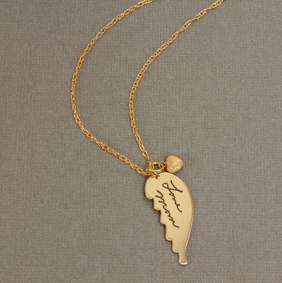 gold angel wing with handwriting, shown from the top