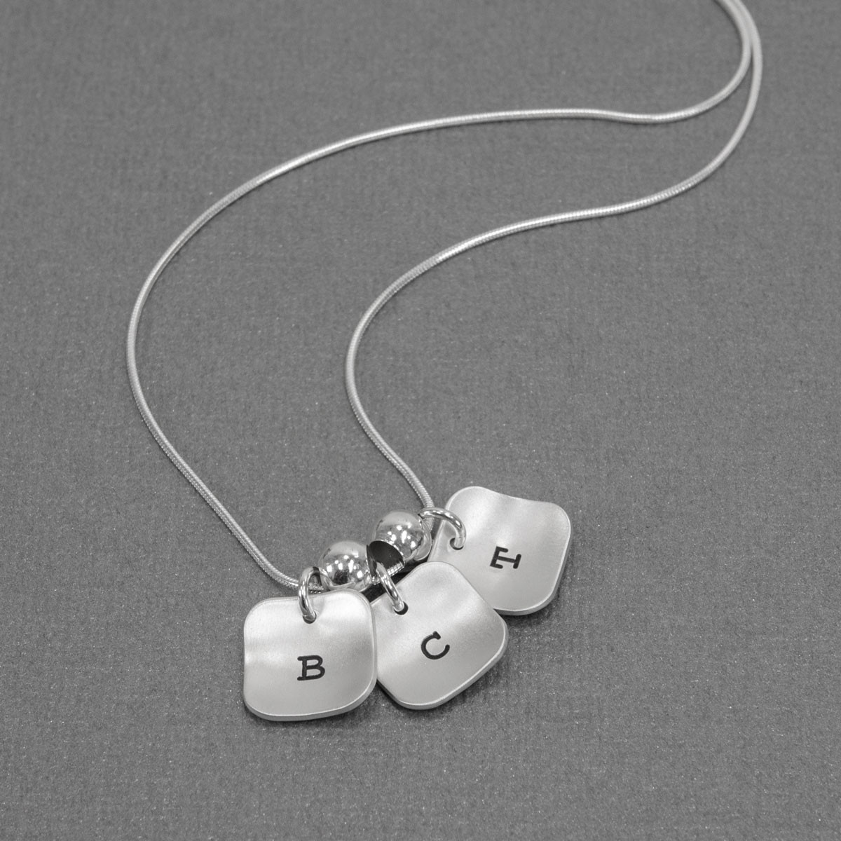 hand stamped brushed silver squares initial necklace, shown on gray