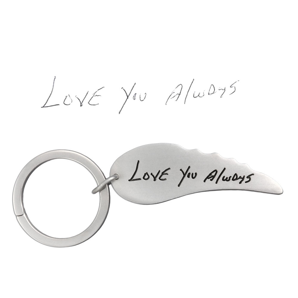 Personalized silver angel wing key ring with your loved one's handwriting, shown with the original handwritten note