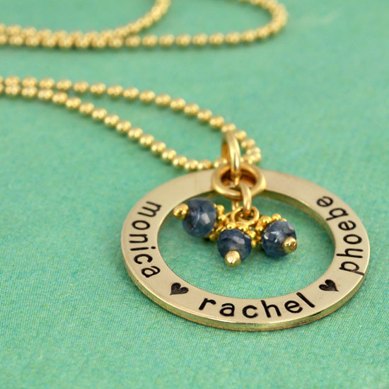 Gold custom hand stamped circle necklace personalized with kids names and birthstones, shown from side