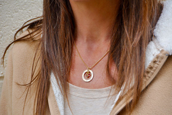 Gold custom hand stamped circle necklace personalized with kids names and birthstones, shown on model