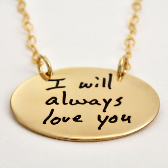 Gold oval necklace with your actual handwriting, shown from the side on white