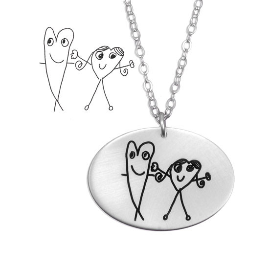 Close up of silver oval charm necklace with kid's artwork, showing original artwork and finished necklace