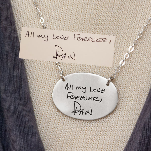 Close up of silver oval charm necklace with handwriting, showing original artwork and finished necklace