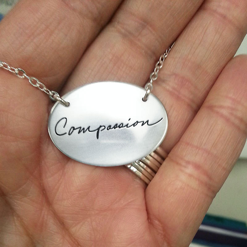 Silver oval charm necklace with a single handwritten word, shown in a hand