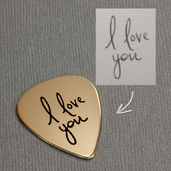 Gold guitar pick with your actual handwriting, shown on with original handwriting used to create the piece