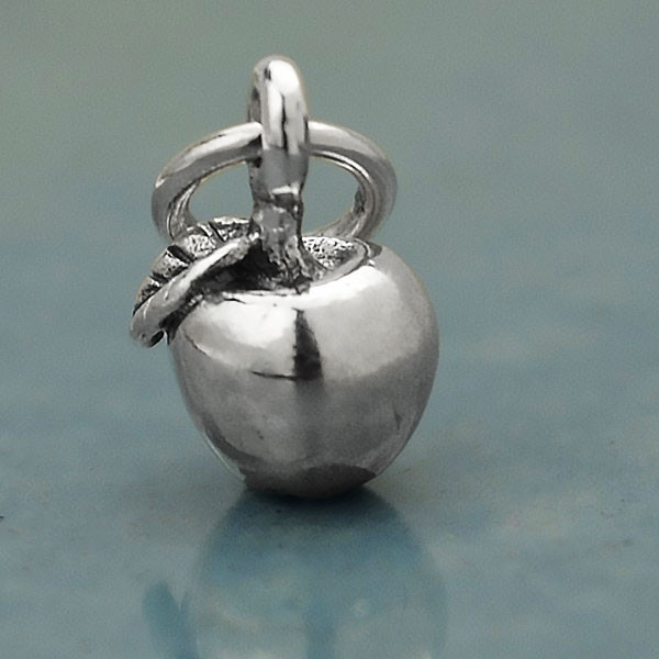 Tiny sterling silver apple charm for teachers, side shown close up