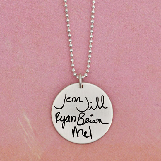 Multiple handwritten names on round silver circle pendant