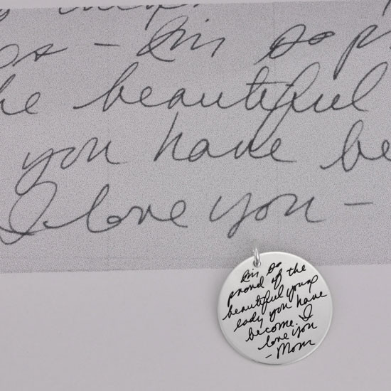 Handwritten message on a silver circle charm