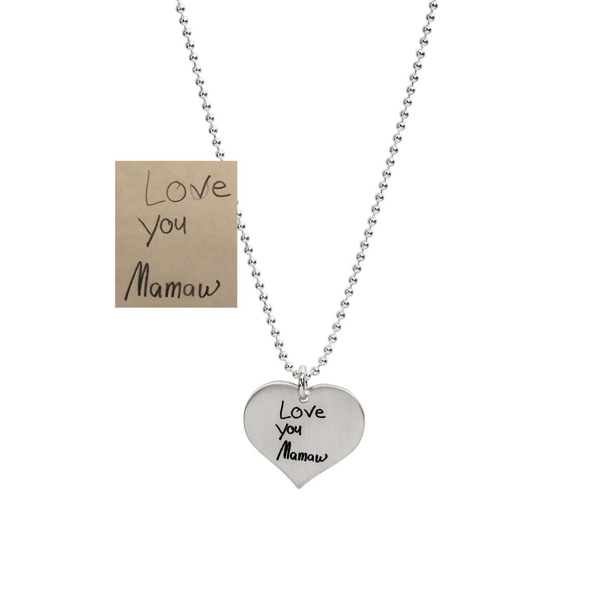 Silver Handwriting heart necklace on white with the original handwriting used to make the necklace