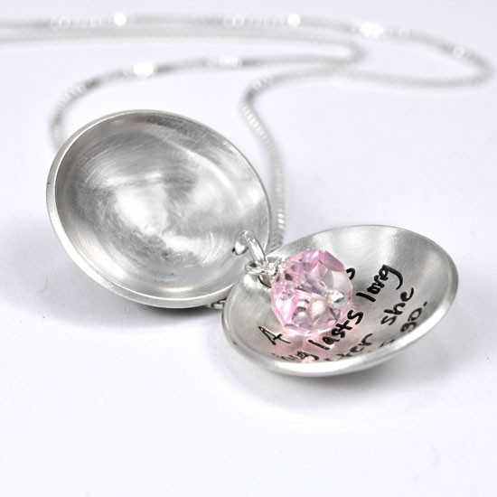 Silver Heart locket for mom with hand stamped message inside, shown open with pink stone from above, on white background