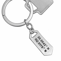 Sterling silver Hand stamped coordinates keychain on white background shown with key