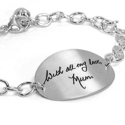 Silver oval handwriting bracelet, with actual handwriting, shown from side on white. close up