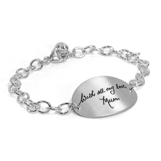 Silver oval handwriting bracelet, with actual handwriting, shown in full from side on white