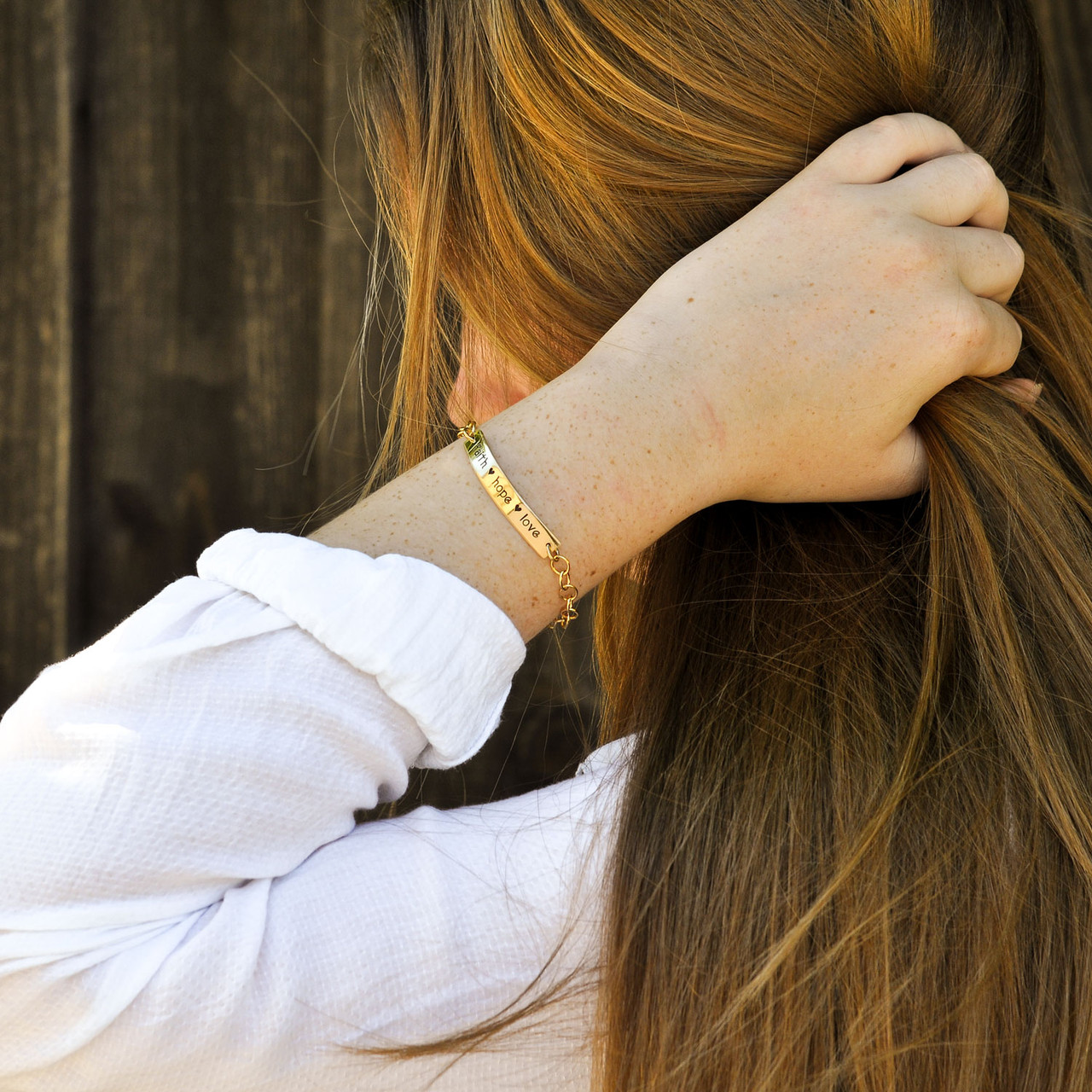 Hand stamped gold ID bracelet, shown on model from side