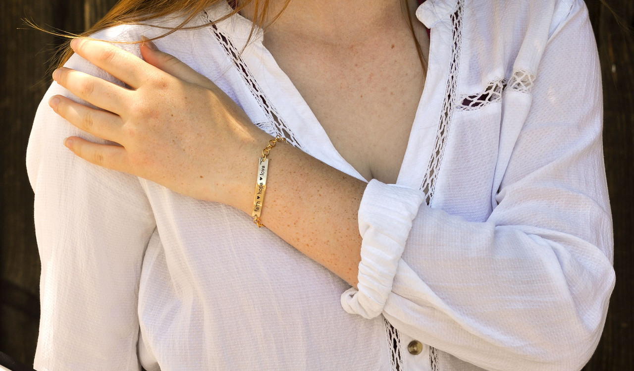Hand stamped gold ID bracelet, shown on model