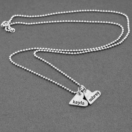 handcrafted silver heart charm necklace, hand stamped with names, shown from the side