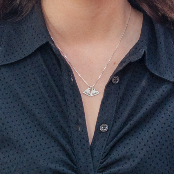 handcrafted silver heart charm necklace, hand stamped with names, shown on model