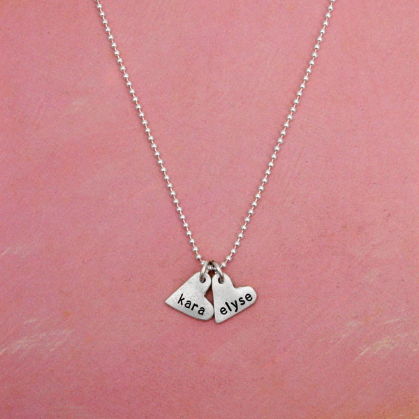 handcrafted silver heart charm necklace, hand stamped with names, hanging on a red background