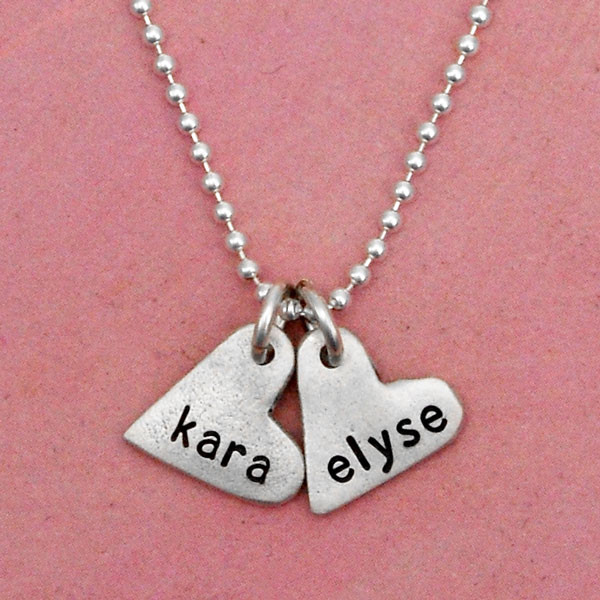 handcrafted silver heart charm necklace, hand stamped with names, shown up close