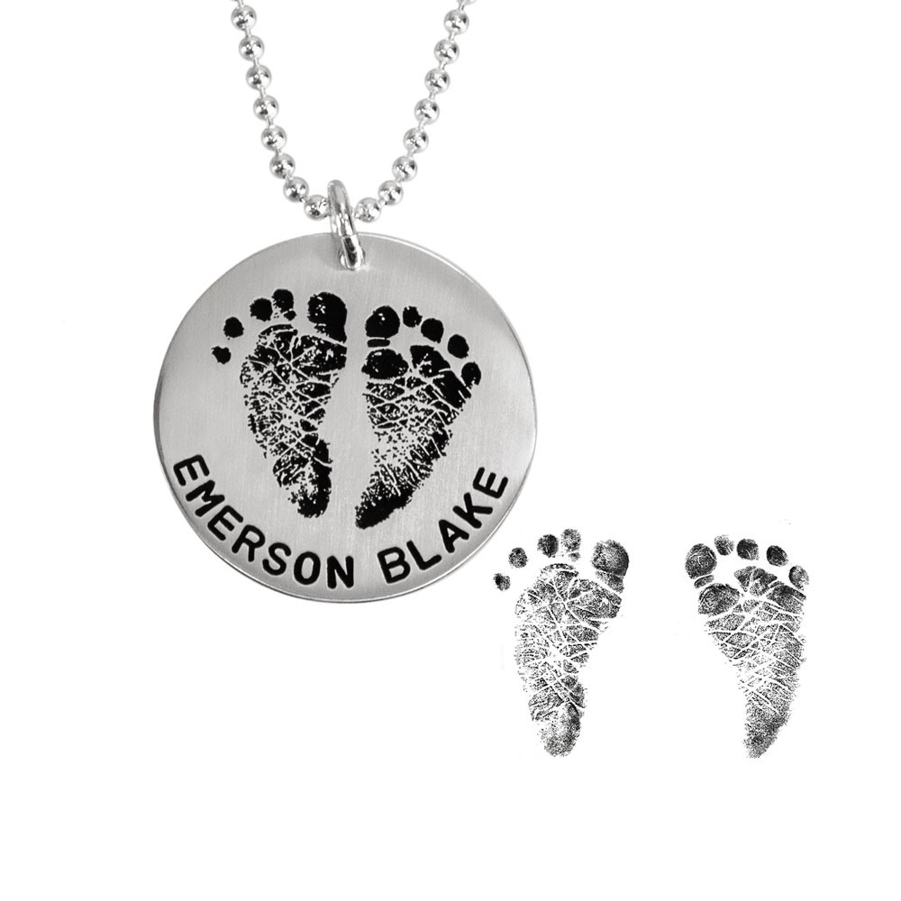 Sterling silver custom footprint necklace with your child's footprints, hand stamped with names and date, shown close up on white with the original footprints