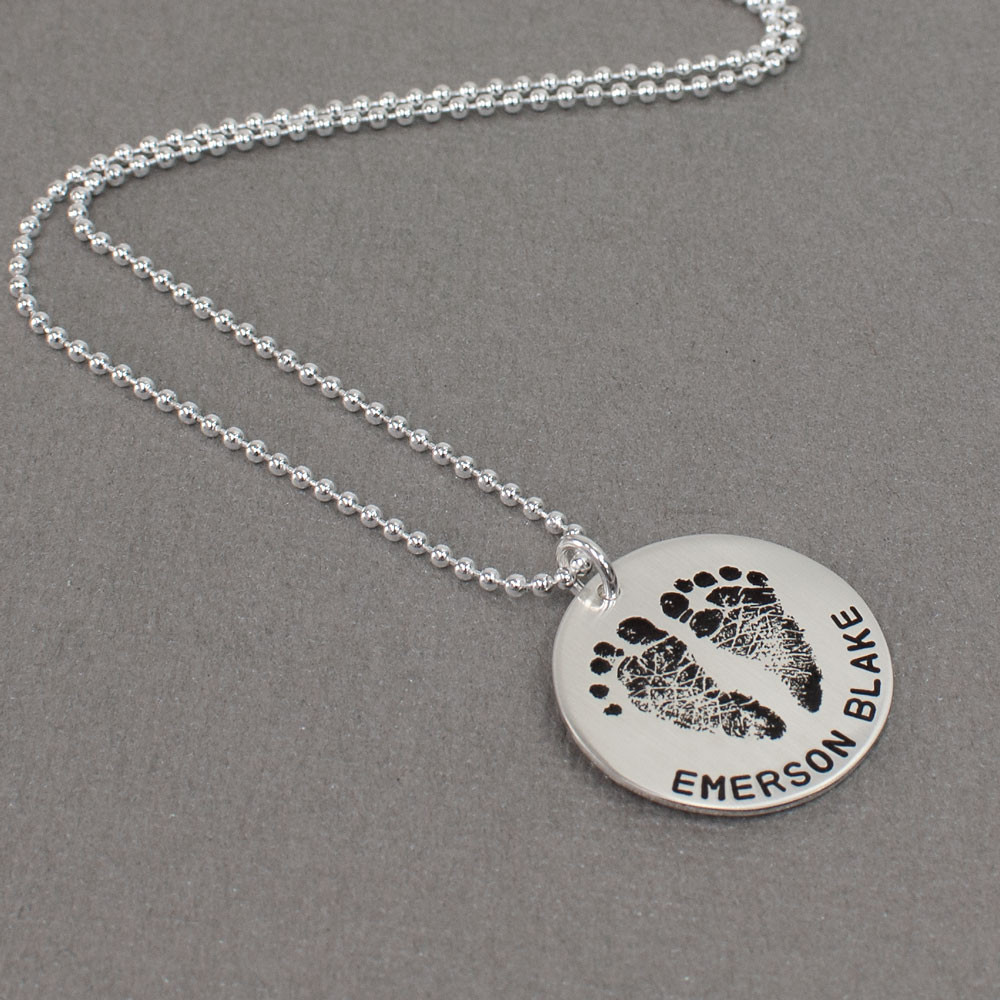 Sterling silver custom footprint necklace with your child's footprints, hand stamped with names and date, shown from the side
