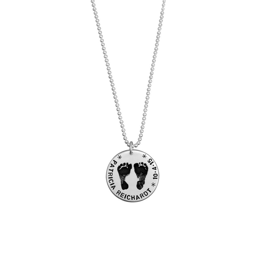 Sterling silver custom footprint necklace with your child's footprints, hand stamped with names and date, shown on white