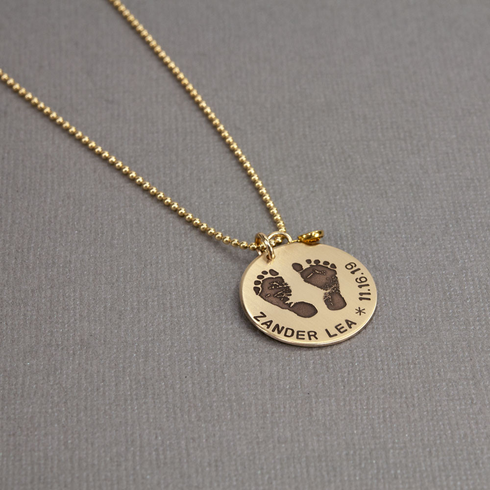 Custom footprints necklace in gold with hand stamping & birthstone, shown from the side