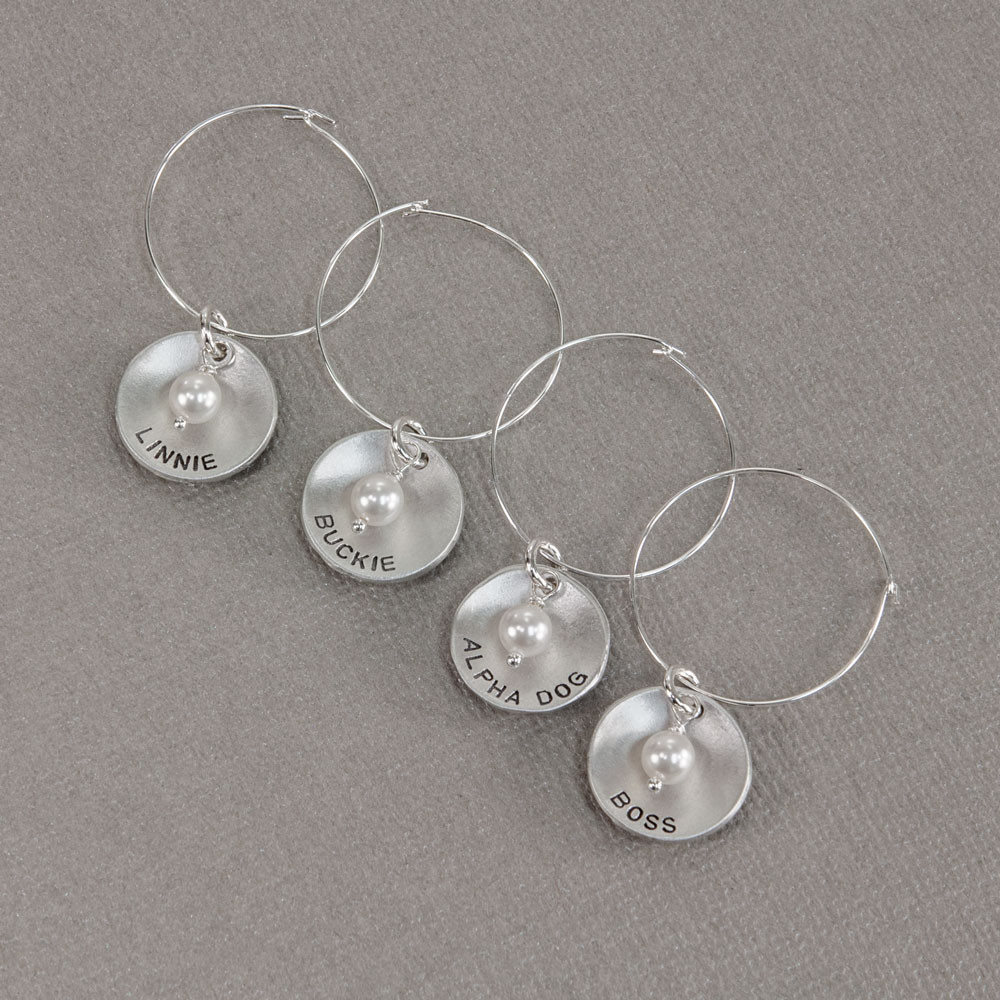 Custom hand stamped wine glass charms in sterling silver personalized with names or words, shown from the top