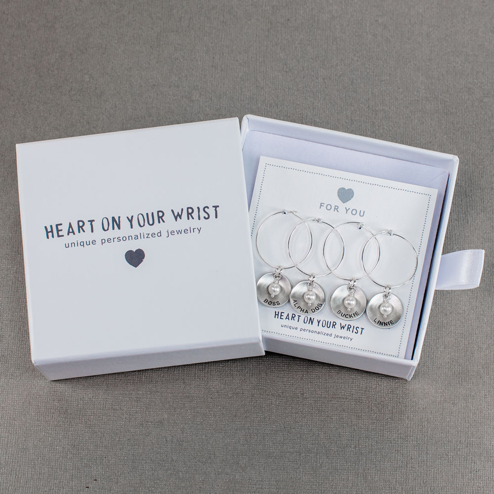 Custom hand stamped wine glass charms in sterling silver personalized with names or words, shown with gift packaging