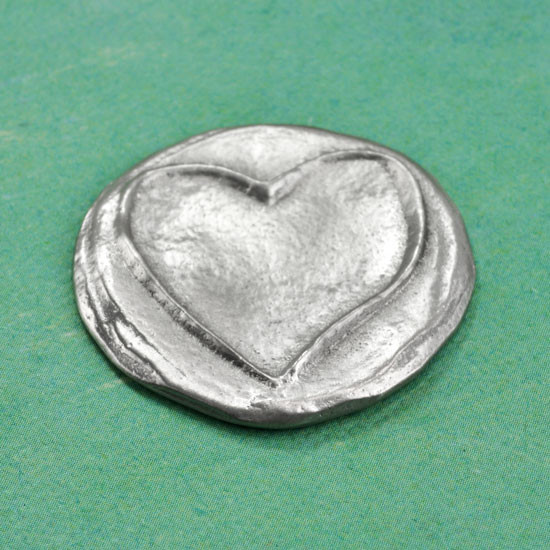 Fine Pewter handwriting pocket charm with a raised heart, showing the front from the side on green background