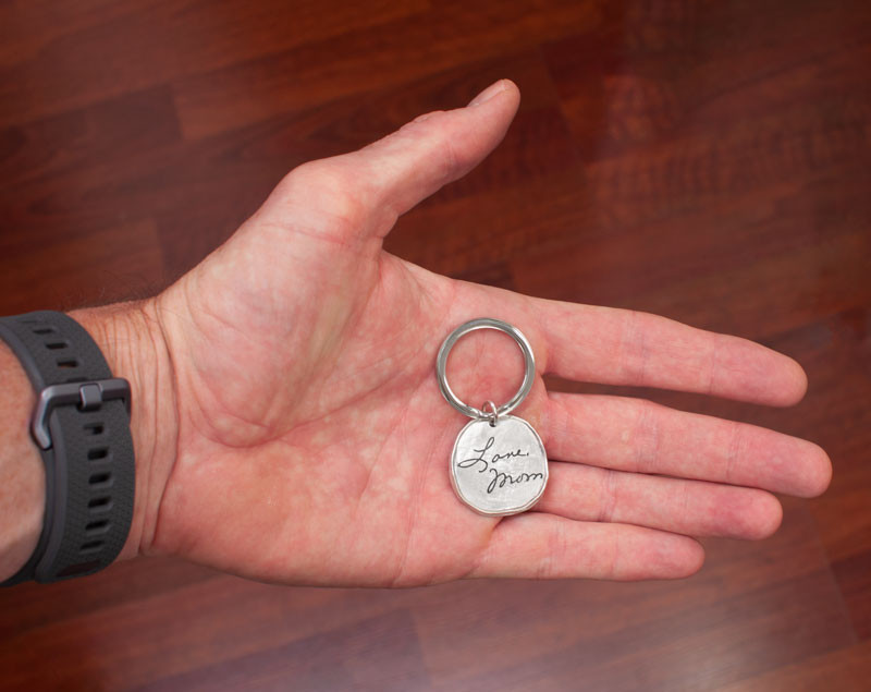 Handwriting on Round Pewter Key Ring , shown in hand