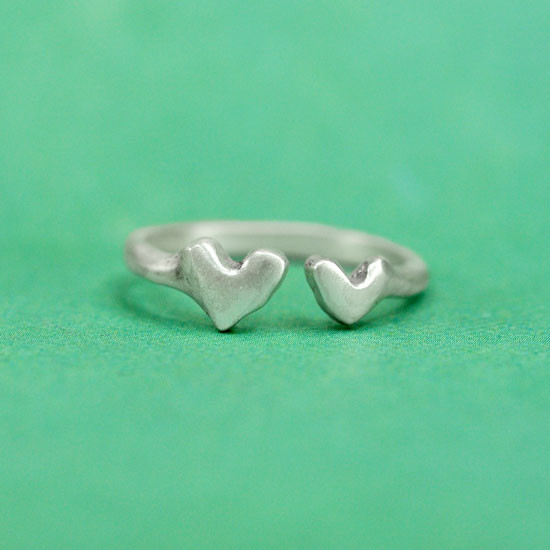 Hand crafted silver ring with two hearts on green