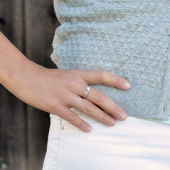 Hand crafted silver ring with two hearts, shown on model hand