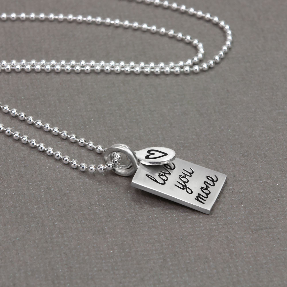 Love you more silver necklace on fine ball chain. shown from the side
