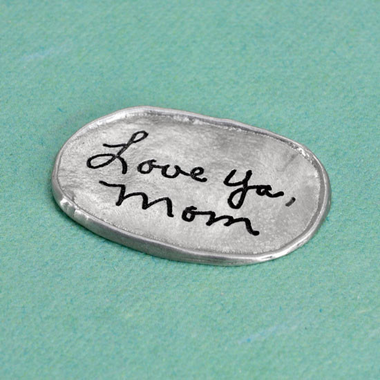 Handwritten note on personalized fine pewter oval pocket charm, shown from the side