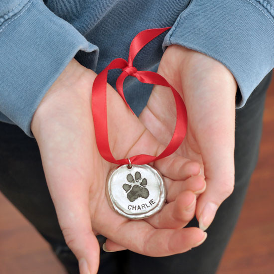Custom fine pewter Christmas ornament, personalized with your dog or cat's pawprint, shown in model's hands