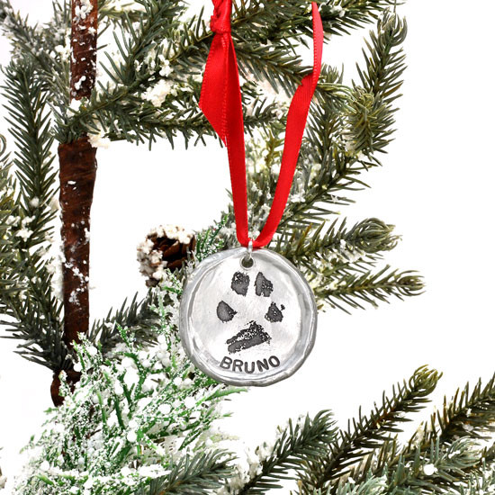 Custom fine pewter Christmas ornament, personalized with your dog or cat's pawprint, shown on a Christmas tree