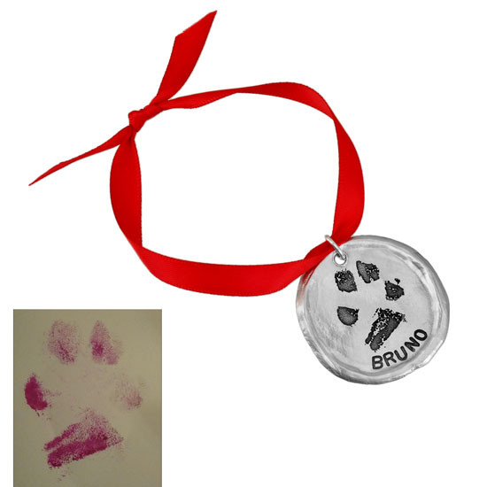 Original pawprint used to create custom fine pewter Christmas ornament, next to the personalized ornament
